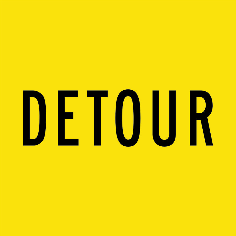 A yellow and black Detour Sign