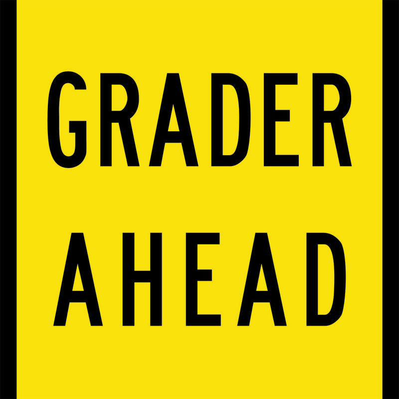 A yellow and black Grader Ahead Sign