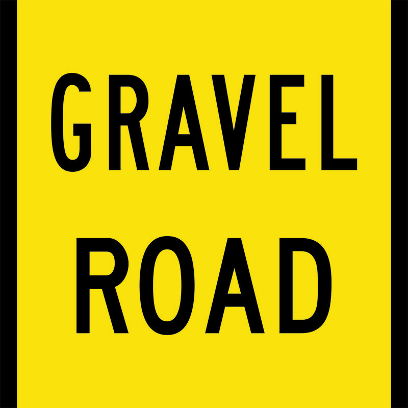 A yellow and black Gravel Road Sign
