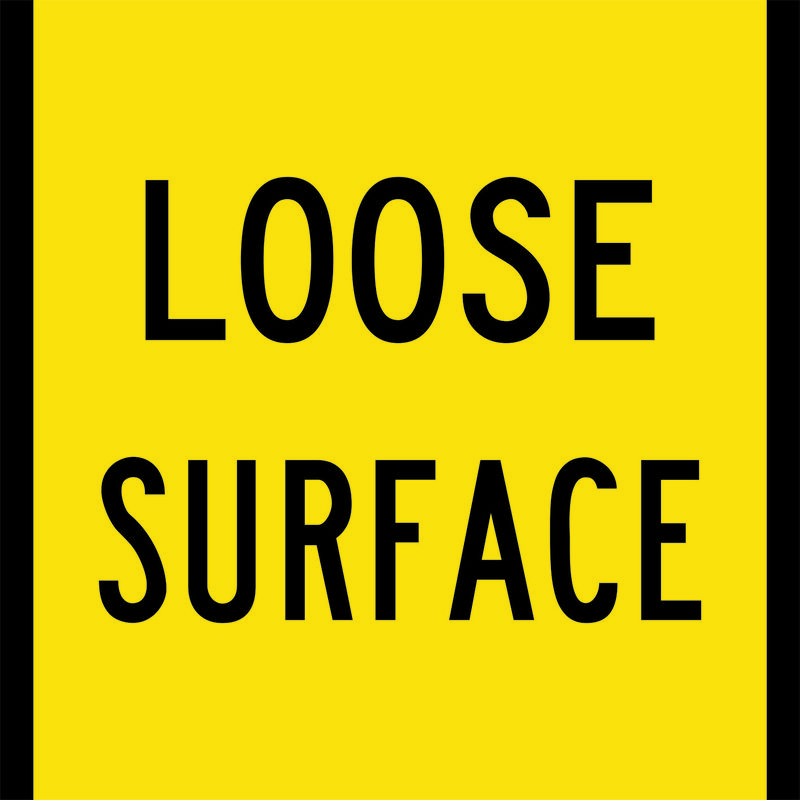 A yellow and black Loose Surface Sign