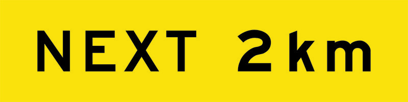 A yellow and black Next 2km Sign