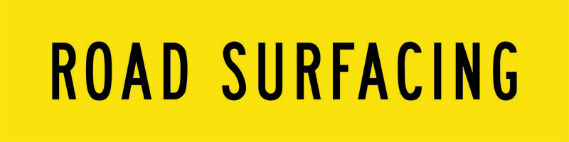 A yellow and black Road Surfacing Sign