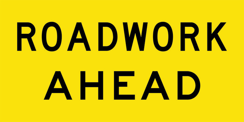 A yellow and black Roadwork Ahead Sign