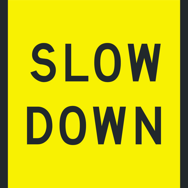 A yellow and black Slow Down Sign