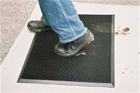 A person wiping dirty boots onto a black Multigard 220 mat