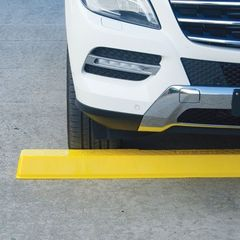 A yellow Plastic Wheel Stop under the front of a white car